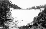 Picture relating to Cotter Dam - titled 'Cotter Dam Wall over flowing into the stilling pond'