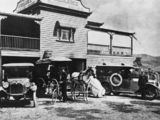 Picture relating to Mount Morgan - titled 'Horse drawn cart with two motor vehicles parked outside the Ambulance Transport Brigade building at Mount Morgan, ca.1921'