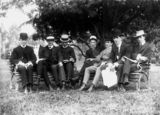 Picture relating to Queensland - titled 'Group of variously dressed men on two garden seats in a park, ca. 1907'