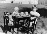 Picture relating to Queensland - titled 'Young girl entertaining Mickey Mouse and other friends at a make-believe tea party, 1930s'