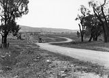 Picture relating to Duntroon - titled 'Duntroon Road now Fairbairn Avenue, Campbell, looking towards Reid with road roller. Site of the War Memorial on the left.'