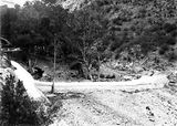Picture relating to Cotter River - titled 'Cotter Dam below the wall;stilling pond is dry. Footbridge across Cotter River on the left.'