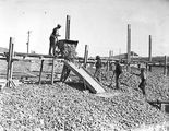 Picture relating to Weston Creek - titled 'Workman pouring screenings from skip at trickling filters - Weston Creek Sewerage Treatment Works'