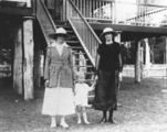 Picture relating to Pialba - titled 'Two women and a child pose in their day clothes at the bottom of a set of stairs at a house at Pialba, 1919'