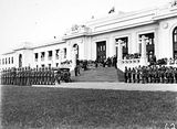 Picture relating to Parkes - titled 'Armistice Day Ceremony with the Royal Military College Cadets on parade in front of Old Parliament House Boy Scouts on the right, View from Parkes Place.'