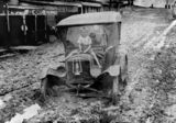 Picture relating to Innisfail - titled 'Boy sitting on the bonnet of a car bogged in mud from the 1925 flood at Innisfail, Queensland'