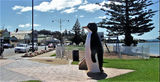 Picture relating to Penguin - titled 'Penguin sculpture shops and coast'
