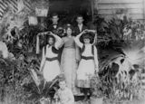Picture relating to Queensland - titled 'Six children pose in fancy dress in a doorway surrounded by staghorn ferns, 1890-1900'